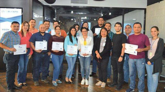 A group of trainees holding passing certificates