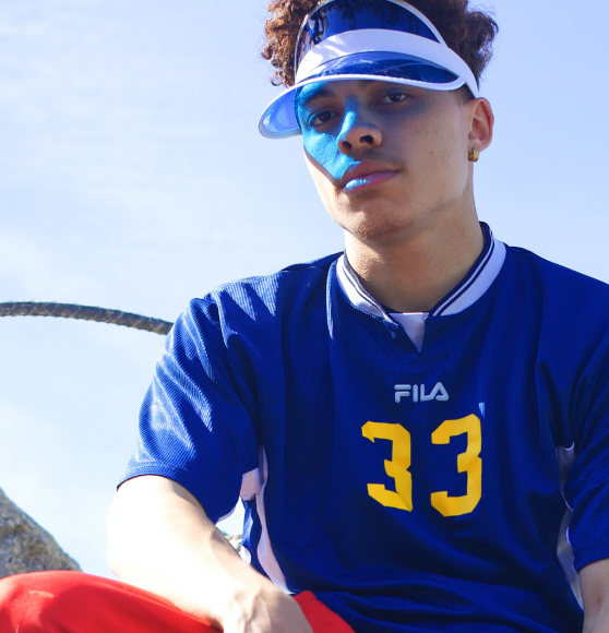 Male model wearing blue sports tshirt and blue visor looking into the camera