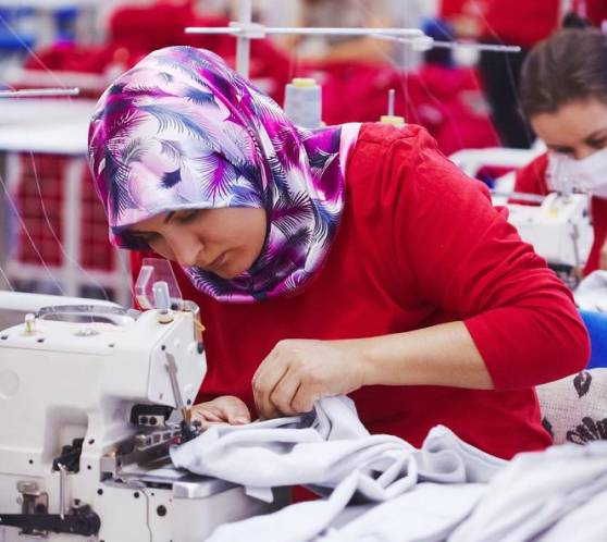 Woman in colourful headscarf using a sewing machine in factory