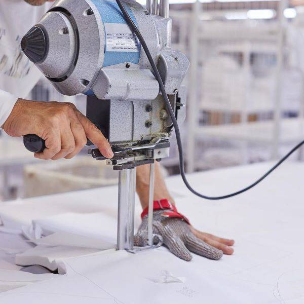 Man wearing protective glove cutting white fabric with cutting machine