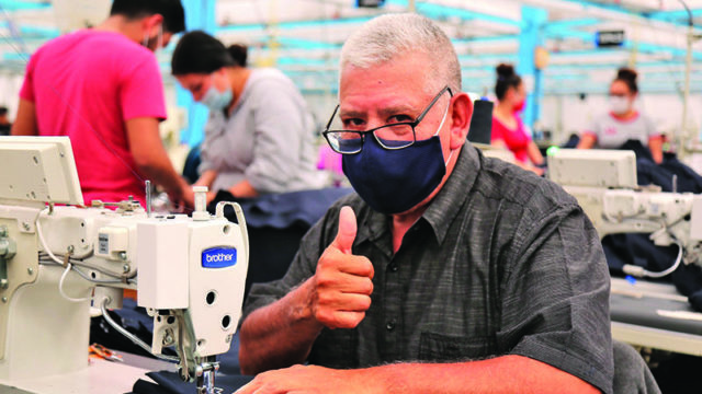 Garment worker working on a sewing machine in Industrias MyR factory, Mexico