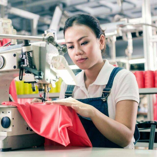 Woman wearing dungarees sewing pink fabric on sewing machine