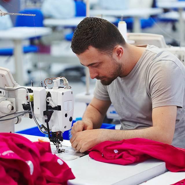 Nam thợ may sử dụng máy may trong dây chuyền sản xuất của Nhà máy