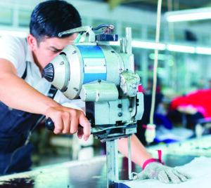 Man using cutting machine in garment factory