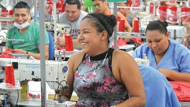 Garment worker smiling on Pinehurst manufacturing floor