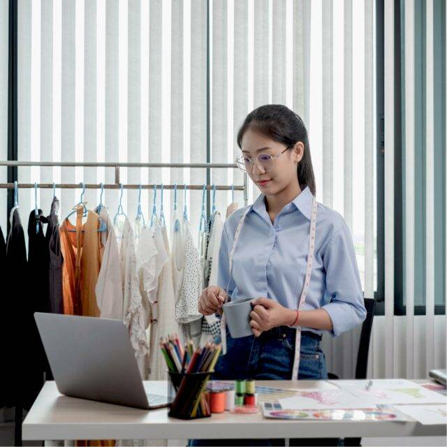 Women standing up at desk in front of laptop with a rail of clothes behind