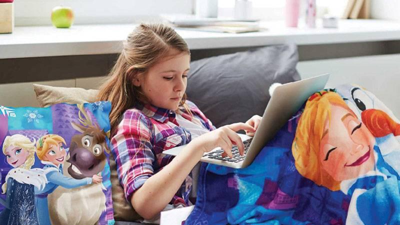 在毯子下的女孩与笔记本电脑