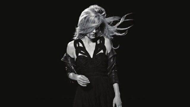 穿着黑色连衣裙,背景为深色的模特