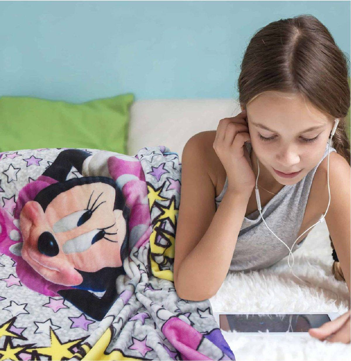 Girl with headphones under Minnie mouse duvet cover