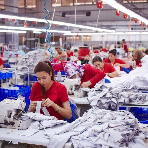 Garment factory production workers wearing red using sewing machines