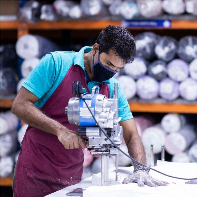 Man wearing protective glove cutting fabric with fabric rolls in the background