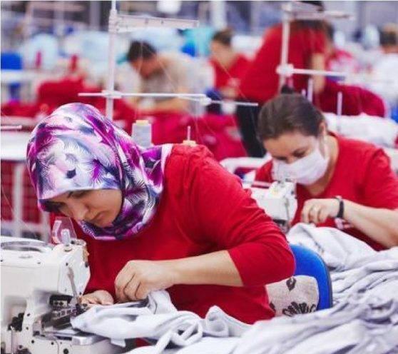 制衣厂生产工人穿着红色服装使用缝纫机