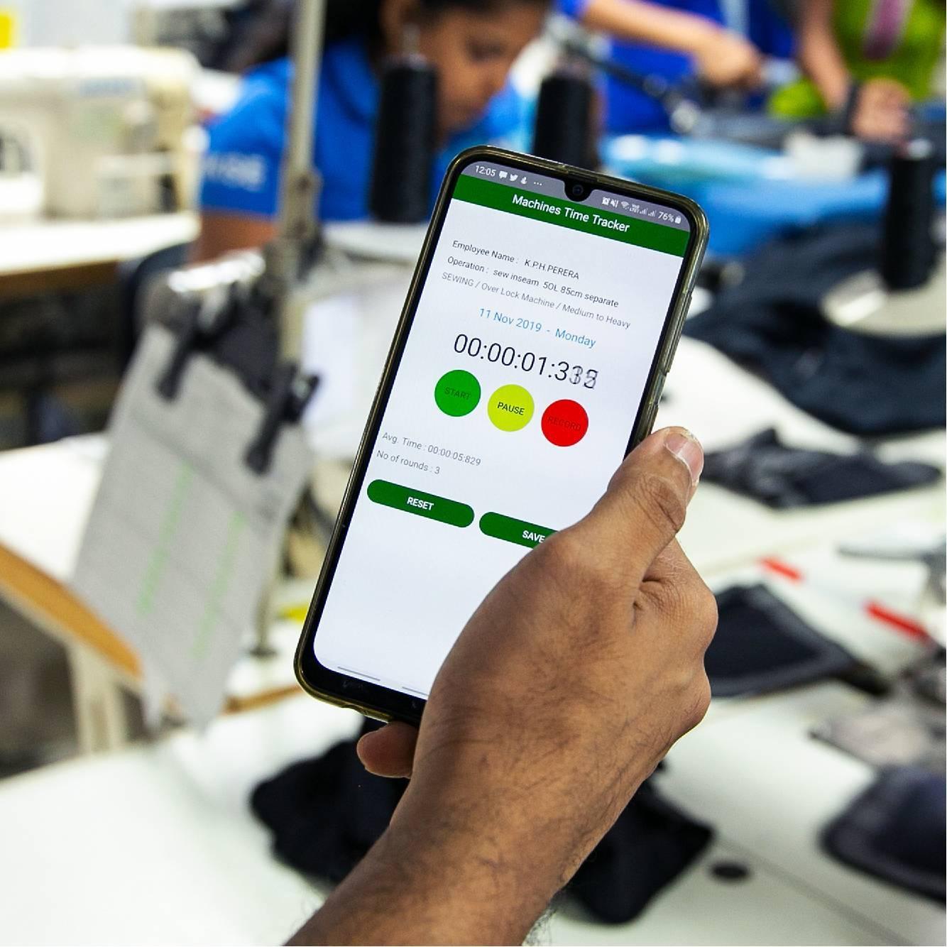 在服装厂手持屏幕上显示Res.Q解决方案的智能手机