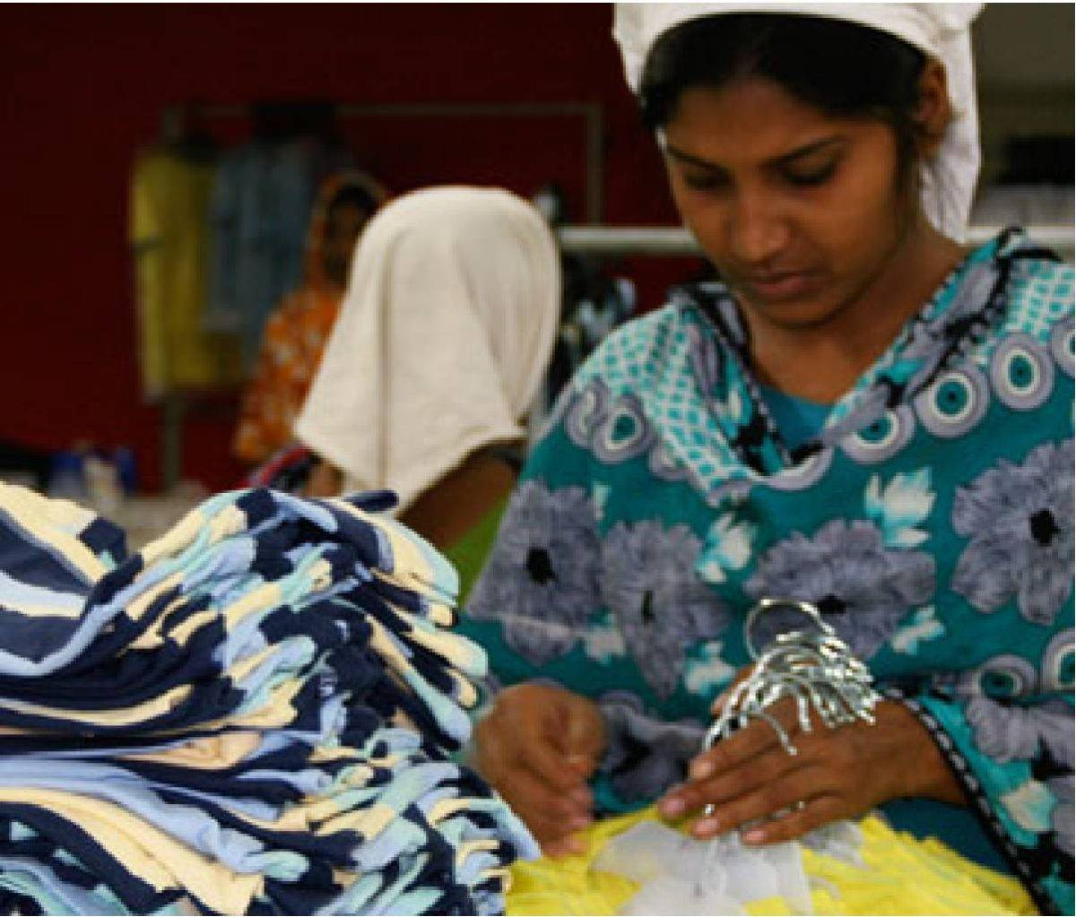 Female Epyllion employee looking at blue and yellow garments in garment factory