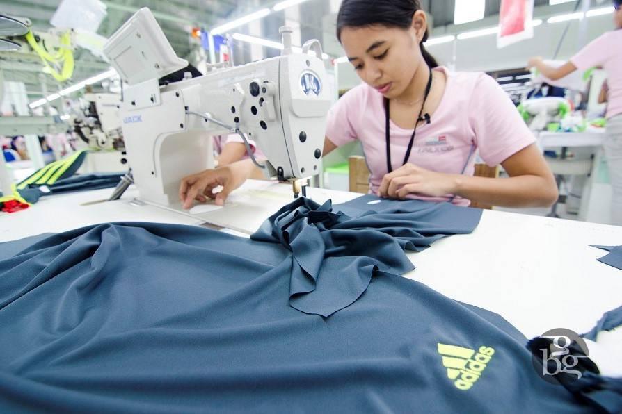 Female Apparel One seamstress sewing blue addidas t-shirt on sewing machine