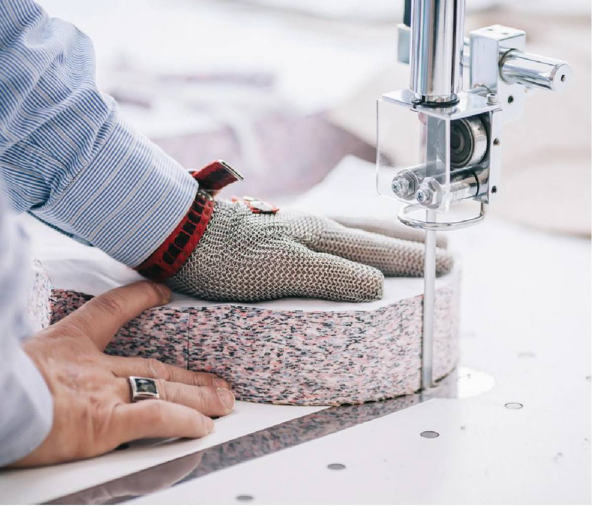 Man wearing safety glove cutting colourful fabric with a cutting machine