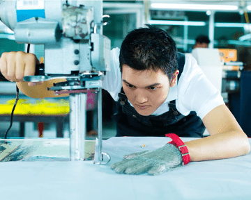 Fabric cutting operator wearing safety glove in a garment factory