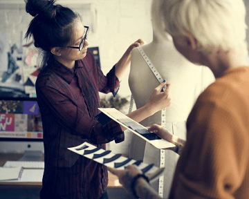 2 名女性时装设计师正在测量模特