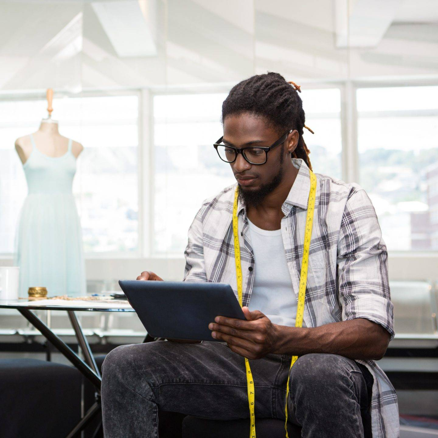 Man with dreadlocks looking at a tablet with yellow measuring tape around neck