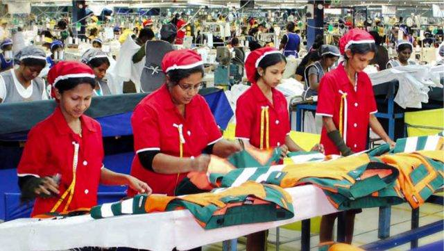 4名女装生产工人在工厂检查服装