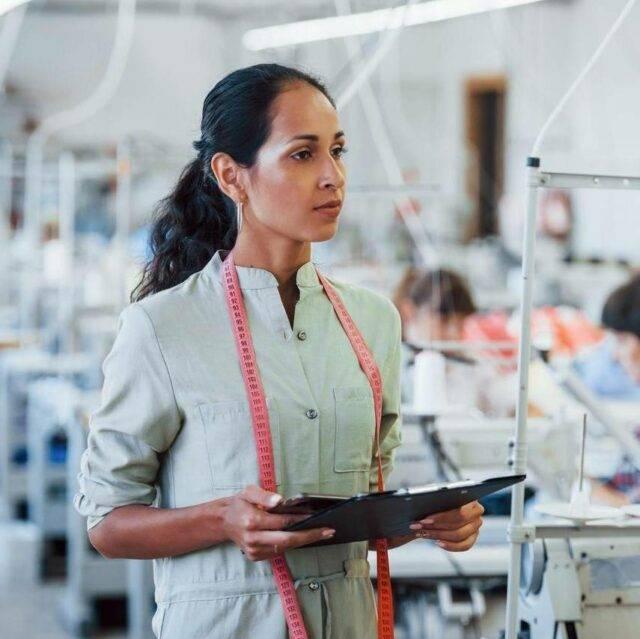 Nữ quản đốc quan sát dây chuyền may bằng máy tính bảng trong xưởng may