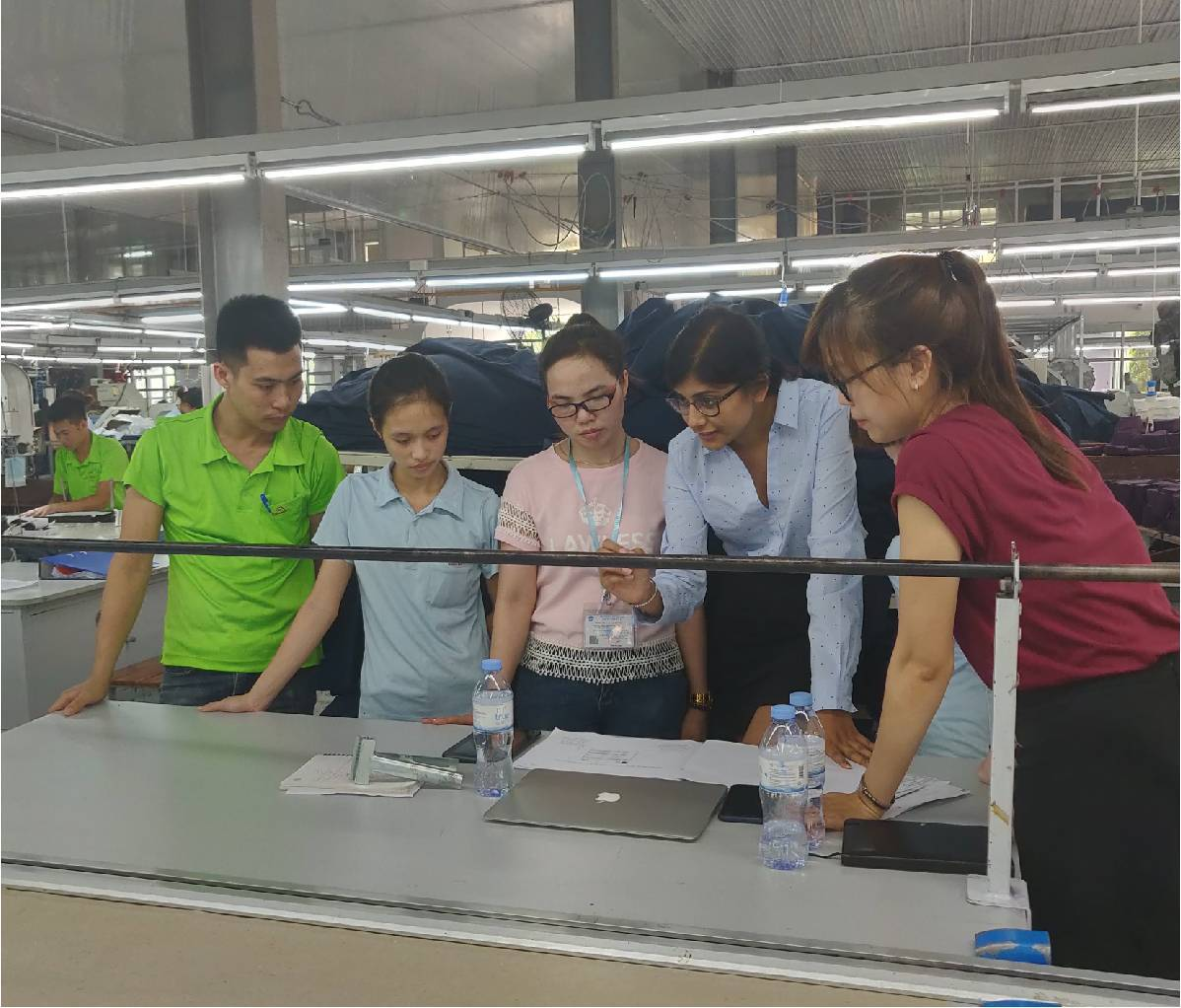 5 Song Hong employees looking at a laptop on cutting table in garment factory