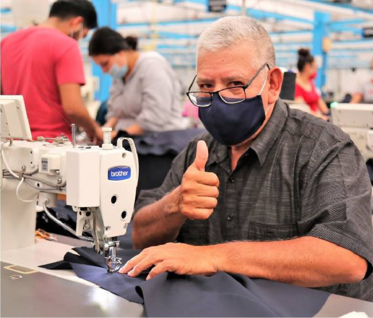 Male Industrias Manufactureras MyR seamstress wearing face mask holding his thumb up to camera