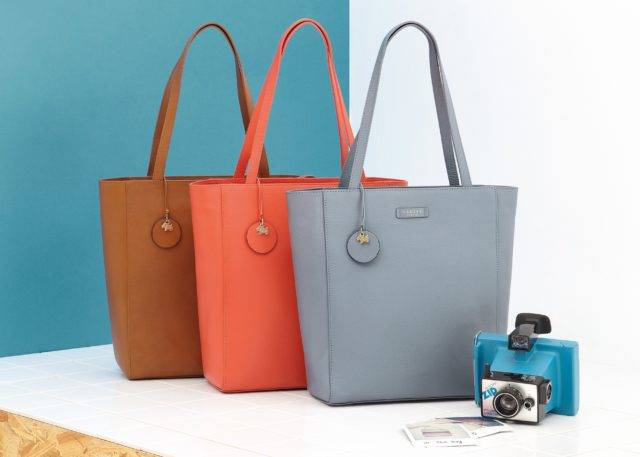 Brown, red and blue Radley bags displayed on white and blue background with camera