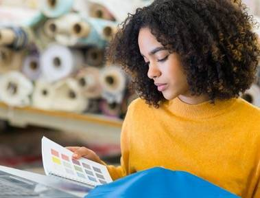 Lady wearing yellow jumper looking at fabric swatches in a fabric warehouse