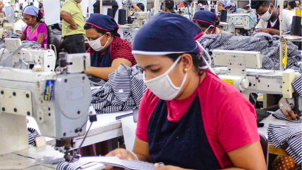 Female seamstress wearing white face mask and blue head scarf in Norwood Fashions garment factory