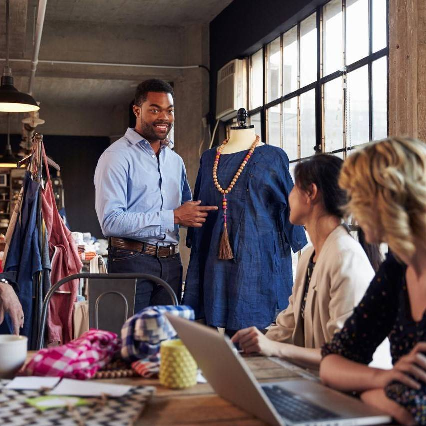 Male fashion designer presenting blue garment to two women in factory