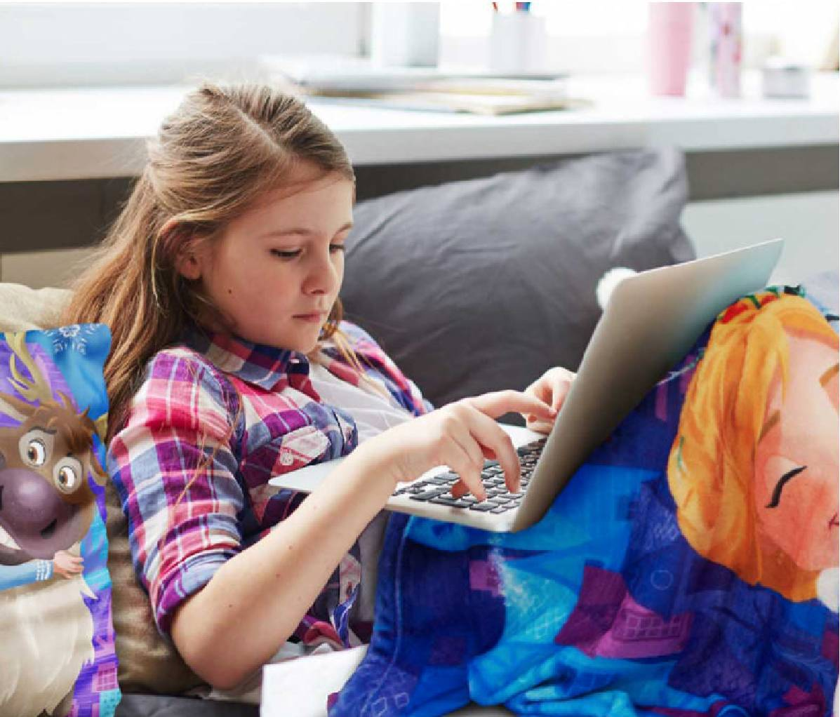 Young girl on laptop in Disney bedding