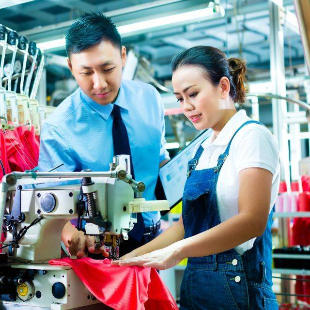Man wearing tie observing female seamstress wearing dungarees using a sewing machine in garment factory