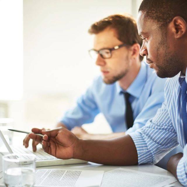 Two business men wearing blue shirts looking at laptop