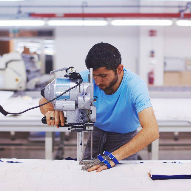 Man wearing protective glove cutting fabric with machine in factory