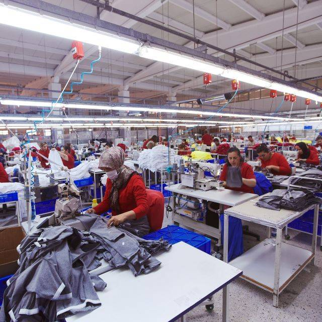 Factory workers wearing red uniform producing blue garments