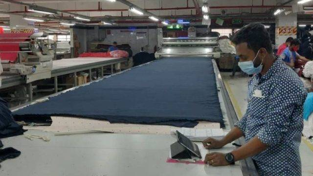 Male Texeurop worker looking an tablet on fabric cutting table in cutting room