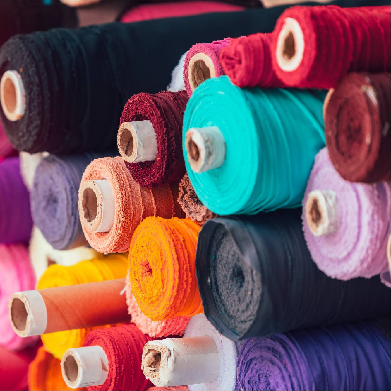 Rolls of colourful fabric in a pile