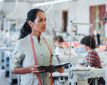 Garment manufacturing supervisor with notepad and tablet in hand