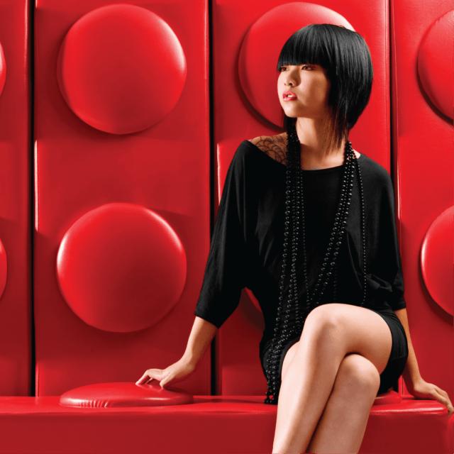 黑色短发女模特在红色背景上身着黑色连衣裙
