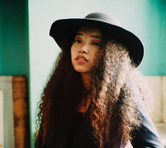 Young women with curly hair wearing black hat and suit