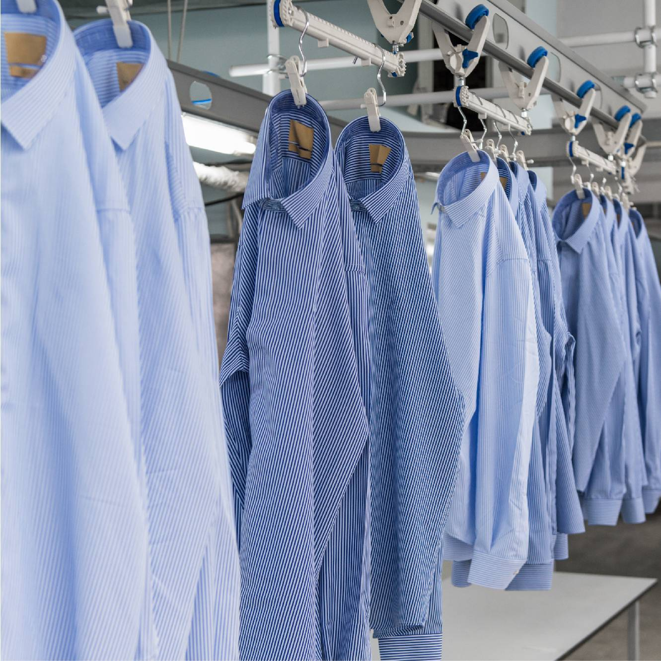 Blue striped shirts hanging in factory